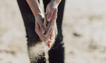 sand flowing from a woman's hands