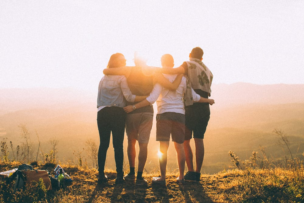 Friends hugging looking at mountain range at sunrise