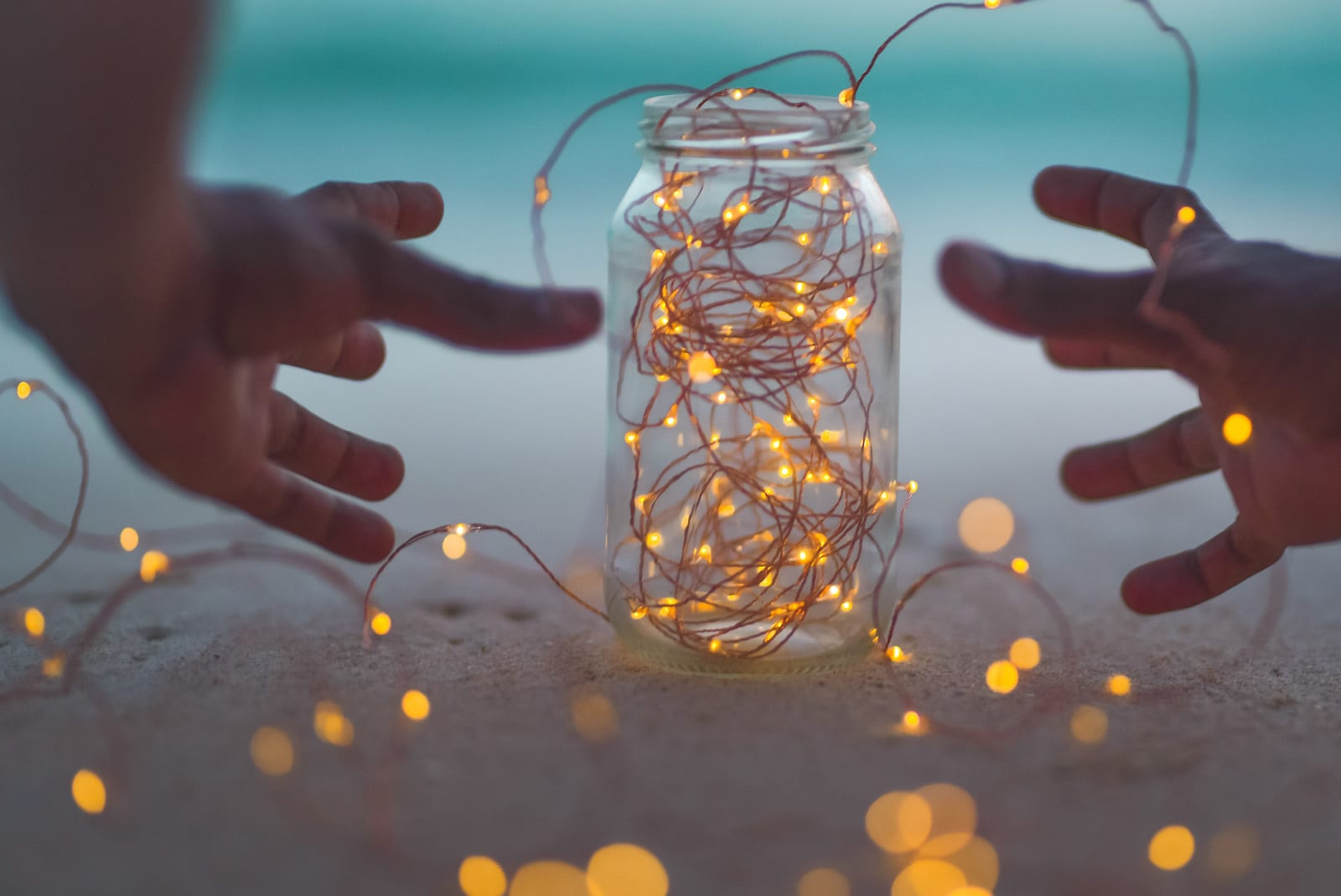 Image of fairy lights in a jar with hands