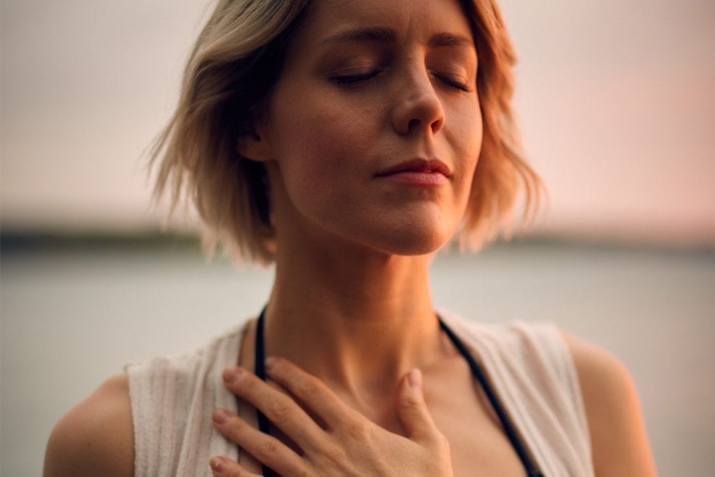 woman meditating, eyes closed hand over chest
