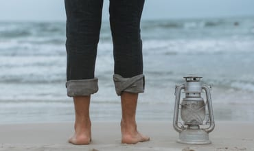 man at beach with pant legs rolled up and lantern beside him