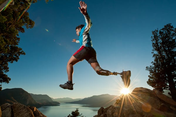 courageous man with prosthetic leg jumping in air while hiking