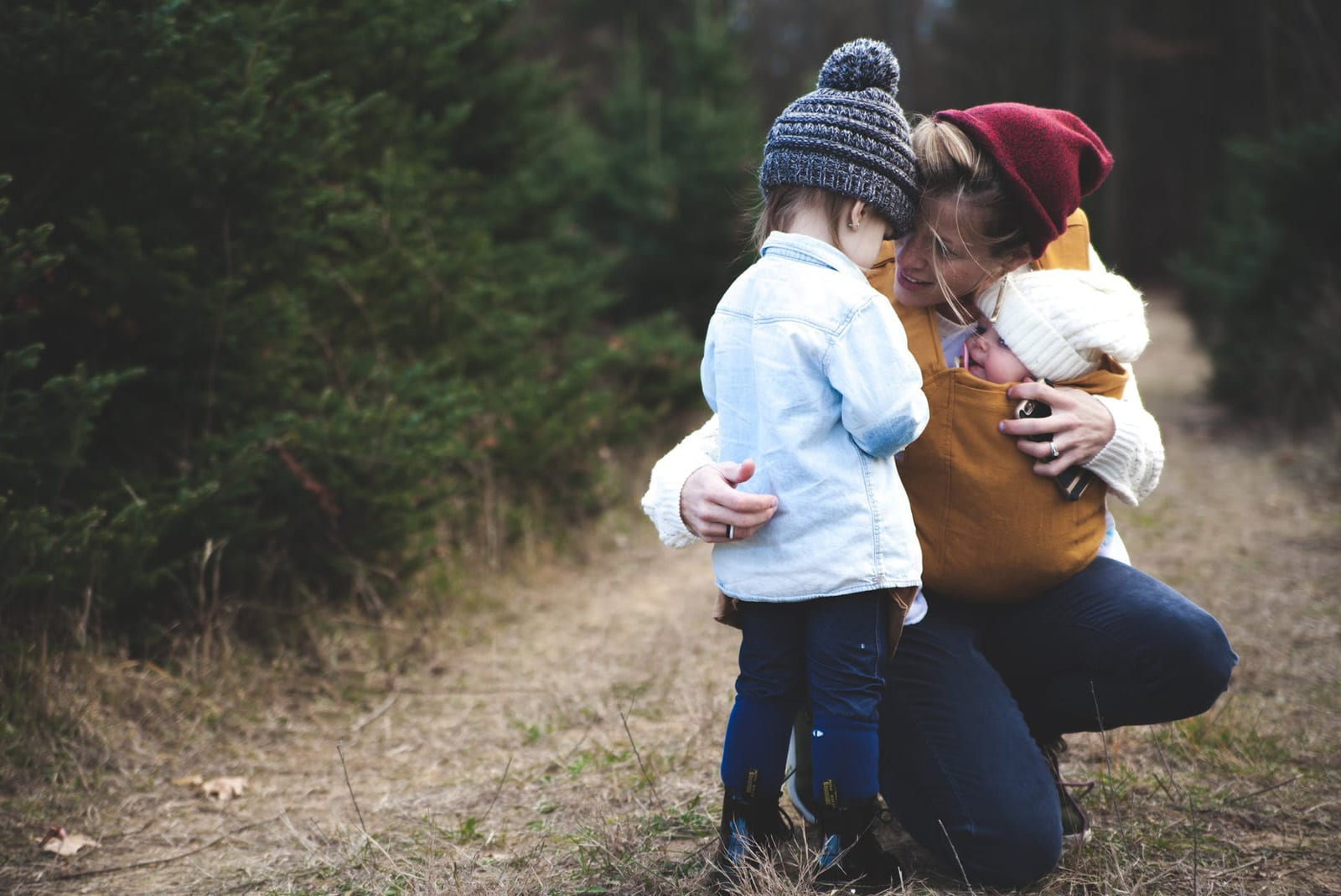 Mother comforting child and holding baby while outside walking amongst trees, Di Beard Personal Coaching