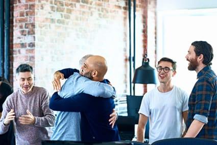 Team exchanging celebratory hug at work, business coaching